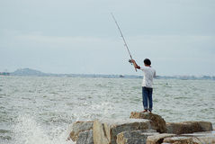 Unidentified man fishing with big wave splashing Royalty Free Stock Images