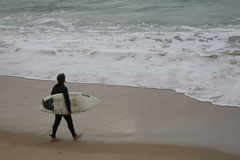 Unidentified man going surfing Stock Image