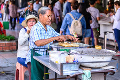 Unidentified man hawker making banana grill for selling at street side in Bangkok, Thailand Stock Images