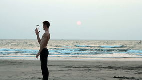 Unidentified man juggling with glass ball on the beach. Goa, India – February 10, 2016: Unidentified man juggling with glass ball on the beach stock video footage