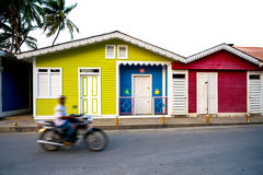 Unidentified man in motion on motorbike passes colorful wooden houses in center of Las Terrenas, Dominican Republic Stock Photos
