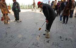Unidentified man paints Chinese characters caligraphy Royalty Free Stock Images