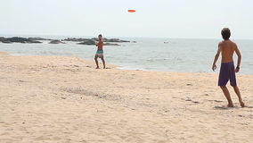 Unidentified man playing Frisbee on the beach stock footage