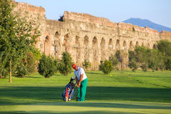 Unidentified man playing golf at the golf course next to the Ancient Roman Aqueduct Stock Photo