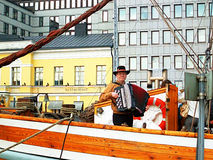 Unidentified man plays the accordion on an embankment in Helsinki, Finland Royalty Free Stock Photos