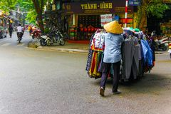 Unidentified man pushes shopping cart with clothes in Hanoi, Vietnam. stock images