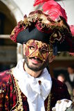 An unidentified man in red fancy dress and mask has a big black hat with red feathers during Venice Carnival Stock Photography