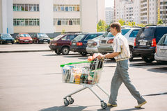 Unidentified man rolls the shopping cart on parking Royalty Free Stock Photography