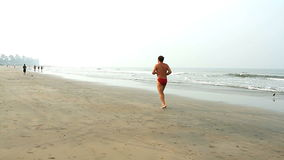 Unidentified man running on the beach. stock video footage