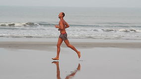 Unidentified man running on the beach. stock footage