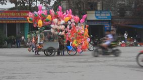 An unidentified man selling the balloons on street. Haiduong, Vietnam, An unidentified man selling the balloons on street stock video footage