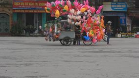 An unidentified man selling the balloons on street. Haiduong, Vietnam, An unidentified man selling the balloons on street stock footage