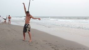 Unidentified man spinning pole on the beach. stock video footage