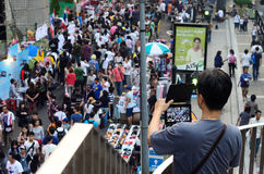 Unidentified man take photo the protesters gather Patumwan intersection to anti government Royalty Free Stock Image