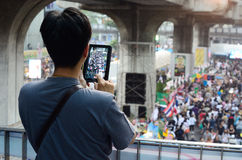 Unidentified man take photo the protesters gather Patumwan intersection to anti government Stock Photo