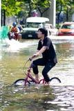 Unidentified man to ride bike through flood Royalty Free Stock Image