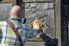 Unidentified man touches his hand to the bas-relief on the Charles Bridge, make a wish Royalty Free Stock Images