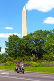Unidentified man travels on motorbike with National Monument seen on the background. Royalty Free Stock Image