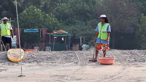Unidentified man and woman cleaning sand beach stock video