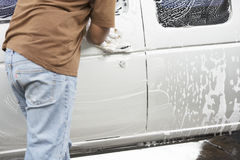 Unidentified man worker washing white car. On Blur background Royalty Free Stock Photo