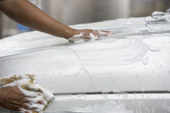 Unidentified man worker washing white car. On Blur background Stock Image