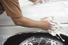 Unidentified man worker washing white car. On Blur background Stock Photo