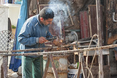 Unidentified man working in the street of Meknes, Morocco. Meknes is one of the four Imper. MEKNES, MOROCCO - FEBRUARY 18, 2017: Unidentified man working in the Stock Photos