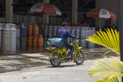 Unidentified men is carrying gas cylinder in motorcycles Royalty Free Stock Photos