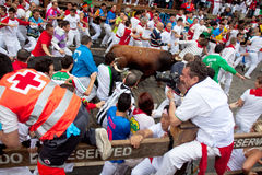 Unidentified men run from bulls in street Estafeta Stock Image