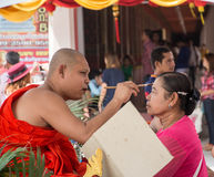 Unidentified monk anoints holy powder on Buddhist forehead, Suphanburi, Royalty Free Stock Photography