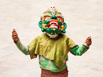 Unidentified monk with ritual bell and vajra performs a religious masked and costumed mystery dance of Tibetan Buddhism stock image