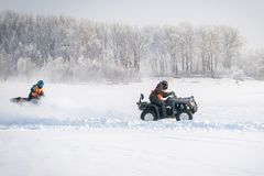 Unidentified motocross rider on quad bike. At Opening motocross season race. winter motocross. ATVs are riding in the field in the snow on the background of Royalty Free Stock Image