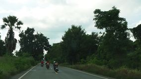 Unidentified motorcycle riders overtake a car on a small road in Thailand stock footage