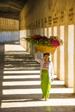 Unidentified Myanmar woman put the flower basket on her head at Shwezigon temple Stock Photo