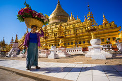 Unidentified Myanmar woman put the flower basket on her head at Shwezigon temple Royalty Free Stock Images