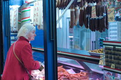An unidentified old lady buying meat Royalty Free Stock Image