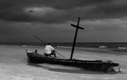 Unidentified old man on wereck boat on the beach with storm clou Stock Photo