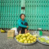 Unidentified old woman selling mangoes on the sidewalk Stock Photo