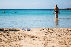 An unidentified and out of focus woman walks into the water leaving behind her sandals royalty free stock photography