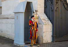 Unidentified Papal Swiss guard standing at the Vatican Museums door in the Vatican. The Swiss guards served since the late 15th century royalty free stock image