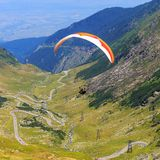 Unidentified paraglider in Balea Lake, Fagaras Mountain, Romania Royalty Free Stock Image