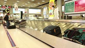 Unidentified passenger takes bag from baggage claim after an international flight stock footage