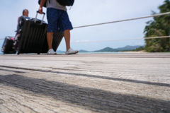 Unidentified passengers disembarking with luggage at pier, unfocused shot. Unidentified passengers disembarking with luggage at pier Royalty Free Stock Image
