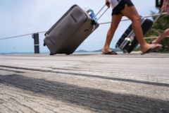 Unidentified passengers disembarking with luggage at pier, unfocused shot. Unidentified passengers disembarking with luggage at pier Royalty Free Stock Images
