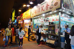 Unidentified people awaiting food from a stall in Hong Kong Stock Photos