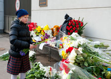 Unidentified people bring flowers. MOSCOW - MARCH 14: An unidentified child brings flowers  to the Japanese embassy as a sign of sorrow and sympathy to the Royalty Free Stock Images
