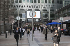 Unidentified people at Canary Wharf walk between clocks. Six public clocks by Konstantin Grcic was designed in competition for thi Royalty Free Stock Photography