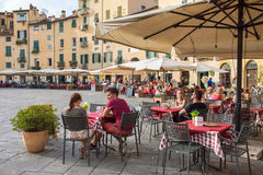 Unidentified people eating traditional italian food in outdoor r. Lucca, Italy - September 14, 2015: Unidentified people eating traditional italian food in stock image