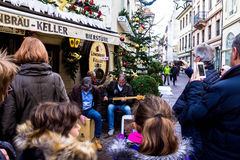 Unidentified people listen  musicians playing on Christmas decorated street Stock Photography