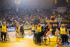 Unidentified people play a friendly game of wheelchair basketbal Stock Photos